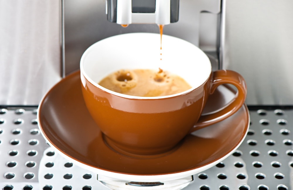 Coffee maker pouring fresh coffee in a cup